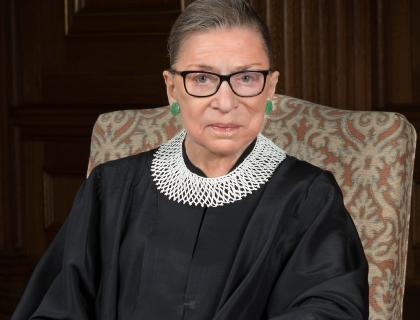 Image of Justice Ginsburg sitting in a chair wearing a scarlet robe (court attire)