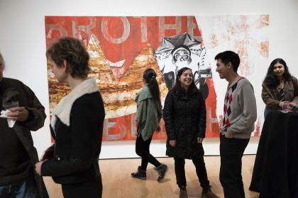 A crowd of people smiling and talking to one another in front of a large collage painting in a Mead Art Museum gallery