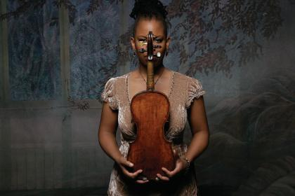 Regina Carter holding a violin in her arms vertically, so that its neck partially covers her face