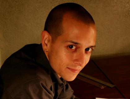 Closeup of Ryan Vigil leaning over a piano and sheet music, with a pair of eyeglasses in his hand