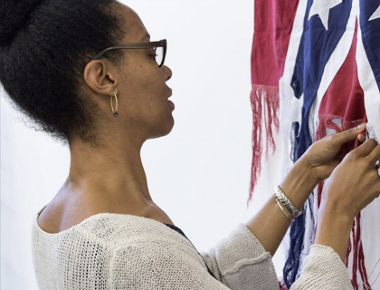 Sonya Clark unraveling a Confederate flag with her hands