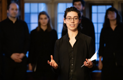 Photograph of Ellen Mutter '18 conducting the Amherst College Choral Society in the Rotherwas Room at the Mead Art Museum. Photo by Jiayi Liu.