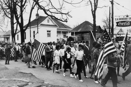 Black-and-white photo of a crowd marching with U.S. flags past houses and trees