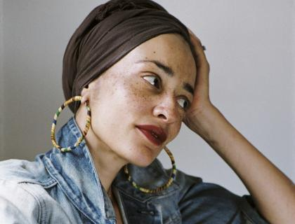 Closeup of Zadie Smith leaning her head on her left hand, wearing a black headscarf, large hoop earrings, red lipstick and a blue denim jacket