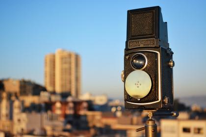 A camera mounted on a pole, with blue sky and a cityscape in the background