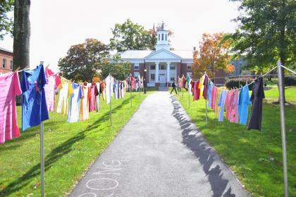Photo has the pathway to Chapin Chapel in the center.  Chapin  is visible in the distance.  Chapin is an old brick building with a white steeple.  Either side of the pathway is lined with T-shirts of different sizes and colors.  BE Strong is written in chalk on the path.