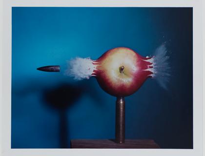 Image of a bullet tearing through an apple that is held up on a metal post