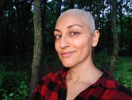 Headshot of Shailja Patel wearing a red and black plaid shirt and standing outdoors among trees