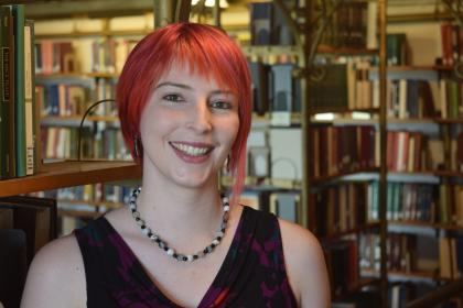 Headshot of Laure Thompson. She is in a library with bookshelves behind her.