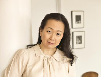 Photo of Min Jin Lee standing indoors, wearing hoop earrings, an off-white blouse and blue jeans