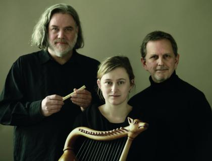 Three musicians dressed in black; two are holding instruments