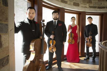 The Parker Quartet standing at a series of sun-lit windows and holding their instruments