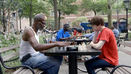 """Still from """"The Prison in Twelve Landscapes,"""" showing people playing chess in a park"""