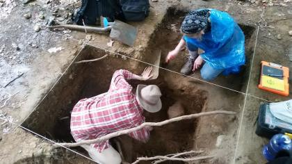 Two people digging in the ground at the Archaeology Field School