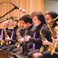 A row of ACJE musicians playing saxophones in front of microphones