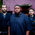 The Tyshawn Sorey Trio standing outdoors in front of a purple building, wearing dark blue shirts and jackets