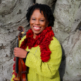 Regina Carter dressed in a brightly colored sweater and scarf, standing in front of a tree trunk, smiling and holding her violin