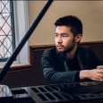 Conrad Tao sitting at a piano, near a window