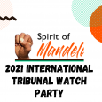 """Center is a clenched fist in the Power Salute to the left of the words """"Spirit of Mandela."""" """"Spirit of"""" is written in plain black lettering, and """"Mandela"""" is written in stylized orange cursive writing. Below this, the words """"2021 International Tribunal Watch Party"""" are written in large black lettering. The background is white, with an black squiggle in the top left, a translucent light blue circle in the top right, and an orange circle overlapping it."""