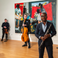 Anthony McGill and the Catalyst String Quartet holding their instruments, standing in a gallery in front of a brightly colored painting