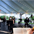 ASO rehearsal in a tent, with the conductor and student musicians wearing masks