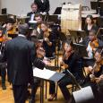 Violinists, drummers and other musicians from the Amherst Symphony Orchestra playing onstage in Buckley Recital Hall, being conducted by Mark Lane Swanson