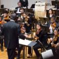 Amherst Symphony Orchestra playing onstage while Mark Swanson conducts