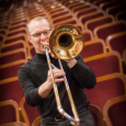 Brian Diehl playing a trombone amid rows of empty theater seats