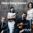 The Chiara String Quartet posing in front of a wall and holding their instruments