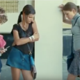 Screenshot of three teenage girls standing in a hallway with their eyes downcast