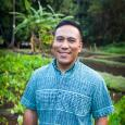 Photograph of Ty P. Kāwika Tengan. He is wearing a blue shirt with a turquoise pattern. He is smiling and standing in a patch of bright green leaves.  He has short dark hair.