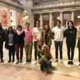 Nine students standing in a row inside a New York City art museum, with a 10th student kneeling in front of them