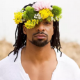 Poet Jericho Brown looks at the camera, one eye obscured by a crown of flowers