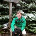 Dr. Stephen Keller crouching in front of a trail sign and snow-covered evergreen trees, with his arms around a black dog