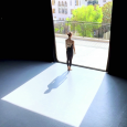 A dancer wearing a black unitard, standing barefoot in a wide doorway, facing away from the camera and toward a balcony that overlooks buildings and trees