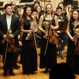 Student soloists standing onstage in front of the rest of the ASO, holding instruments and bouquets of flowers