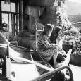 Black-and-white image of two women sitting amid the rubble of houses