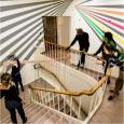"""Gatson and four students standing around a staircase, looking at the """"Halls Walls"""" mural"""