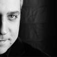 Black and white photo showing the left half of Jeremy Denk's face in front of a dark background