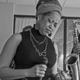 Black-and-white photo of Samirah Evans holding a microphone and standing amid other musicians