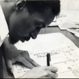 Black-and-white closeup of Julius Eastman hunched over a piece of white paper, writing music with a black pen