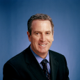 Closeup of Andrew C. Kuchins '81 smiling and wearing a blue shirt, dark jacket and dark tie, in front of a blue background
