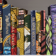 Detail from Shonibare's artwork: books lined up on a shelf, each with a brightly patterned cover