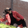 Y. Sung image: A young woman posing outside a brick building, wearing a black COVID mask, black shirt and pants, and long red coat