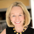 Closeup of Doris Kearns Goodwin smiling and wearing white pearl earrings, black-and-gold beaded necklace and black dress