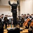 Mark Lane Swanson leaps into the air in front of ASO musicians