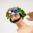 Image of the head, neck, shoulders and raised left hand of a human figure with a colorful floral headdress and a black strap across his mouth