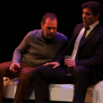 "Two male characters sitting next to each other onstage during ""The Scarlet Professor"""