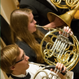 Closeup of several students playing French horns
