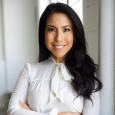 Adriana Villavicencio smiling and wearing a white blouse, with her arms folded in front of her